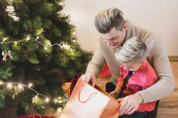 Father and son with bag next to christmas tree