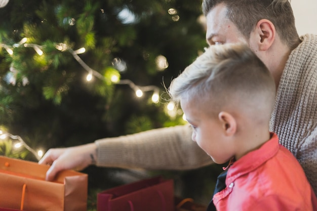 Father and son with bag in front of christmas tree