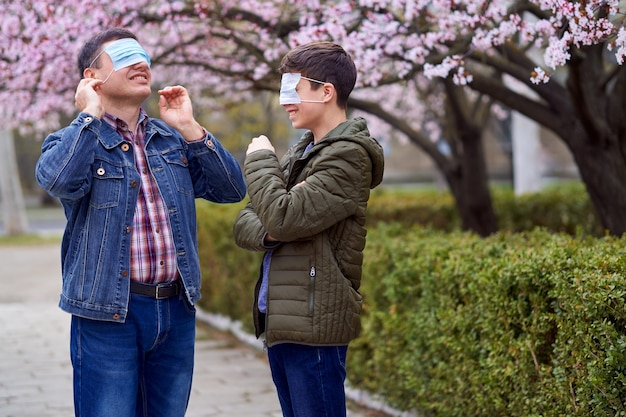 Father and son with a face mask are in the city outdoor, blooming trees, spring season, flowering time - concept of allergies and health protection from dusty air