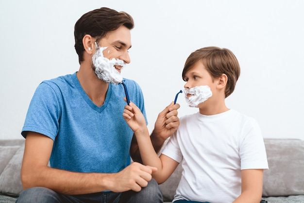 Father and son with foam on faces shaves each other.