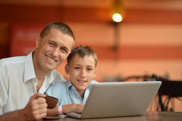 Father and son with laptop at the table