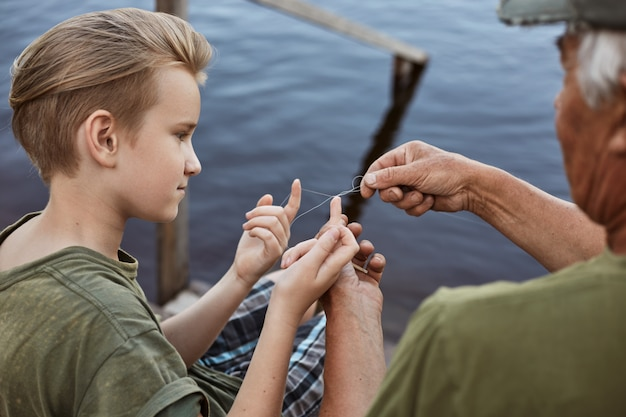 Father and son on wood pontoon, dad teaching his young son to untangle knot on fishing line, family spending time together while catching fish near lake.