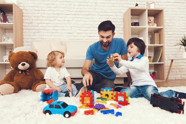 Father and sons is playing with toys.