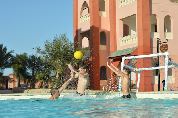 Father and sons playing water polo in swimming pool
