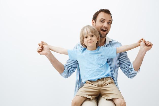 Отец проводит большое время с милым сыном. портрет радостного красивого европейского ребенка с витилиго, сидящего у папы на коленях и раскинувшего ладони