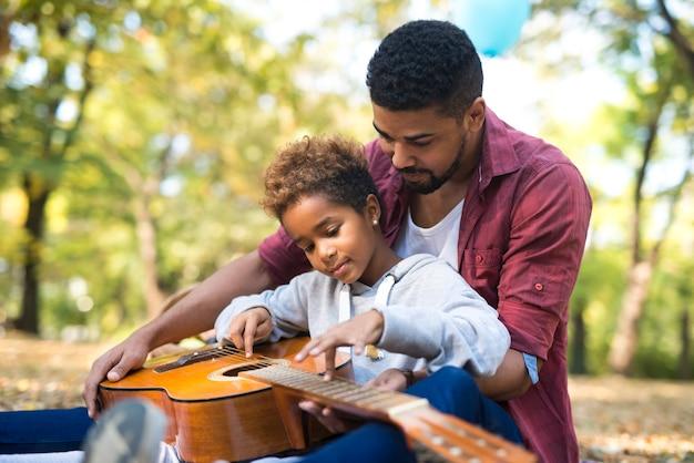 父は娘と一緒に時間を過ごし、ギターを弾く