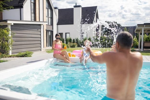 父は水をはねかけます。父は家の近くのプールで彼の娘と妻に水をはねかける