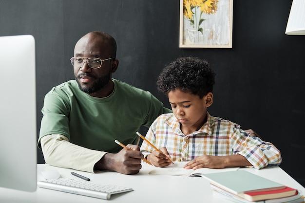 집에서 아들과 함께 공부하는 아버지