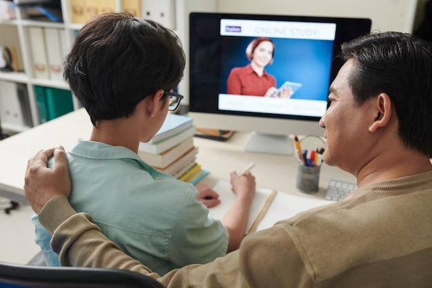 Отец поддерживает своего сына-подростка, который учится на дому из-за пандемии коронавируса