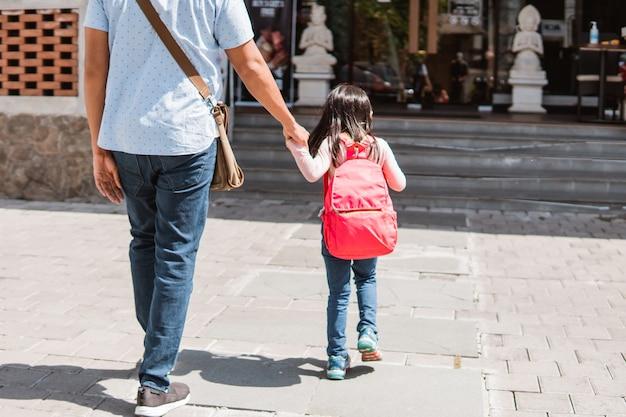 娘と一緒に学校へ散歩する父