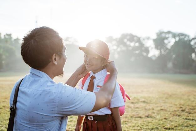 朝、娘を小学校に連れて行く父