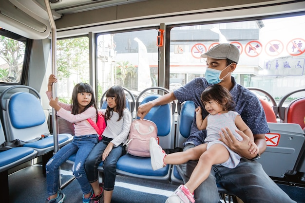 Father taking his daughter to school by riding bus public transport with mask