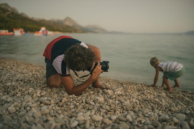 Отец фотографирует своего сына, играющего с галькой на пляже, на камеру dslr