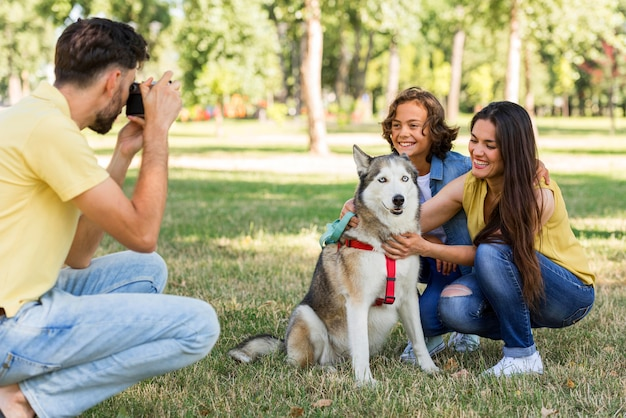 Отец фотографирует мать и сына с собакой в парке