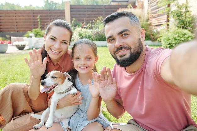カメラで手を振っている彼自身と彼の家族の自撮り写真を撮る父