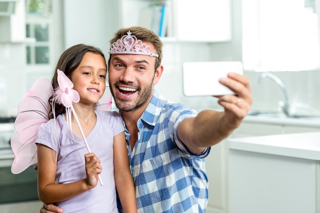 Father taking selfie with daughter in fairy costume