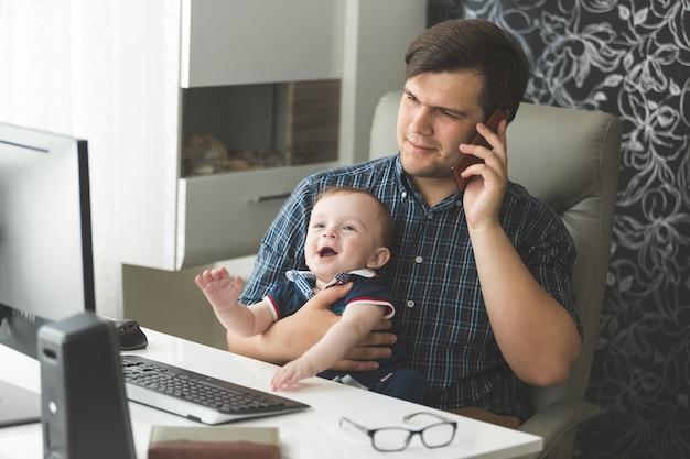 전화로 이야기하고 아기를 돌보는 아버지