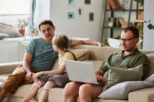 彼らがラップトップで働いている他の人と部屋のソファに座っている間、父は娘と話している
