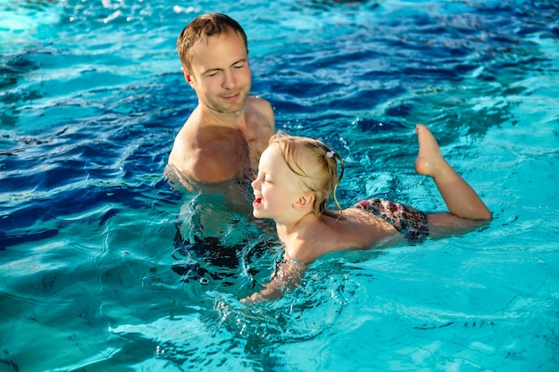 Father teaches daughter to swim in the pool