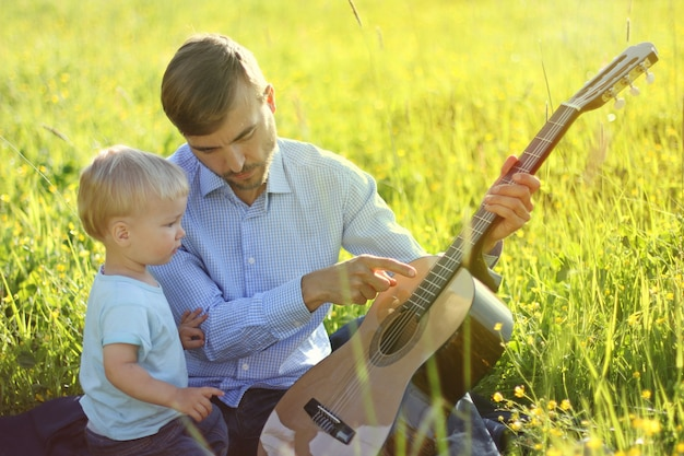 Father teaches his son to play guitar. time together dad and son.