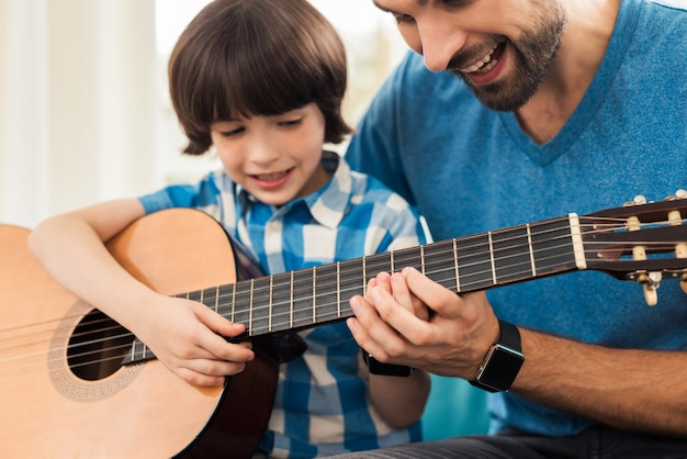 The father teaches his son to play the guitar