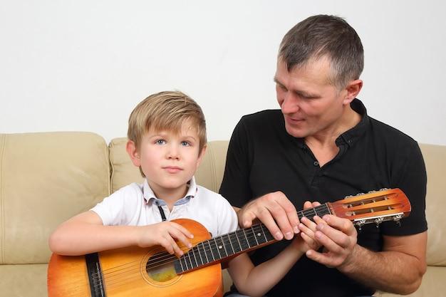 Отец учит сына игре на гитаре