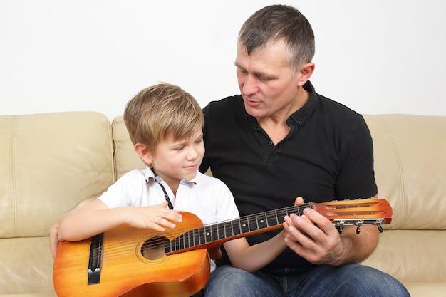 父は息子にギターを弾くように教えます