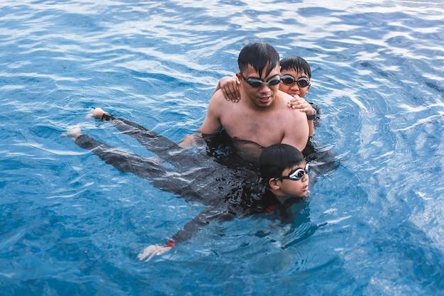 Отец учит сына плавать в бассейне
