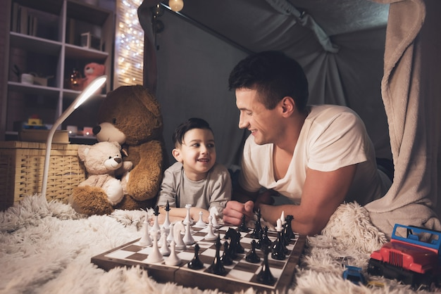 Father teaches little son how to play chess at night at home