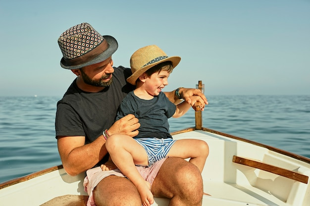 A father teaches sailing to his son in a classic boat