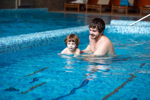 Father teaches son to swim in the pool.