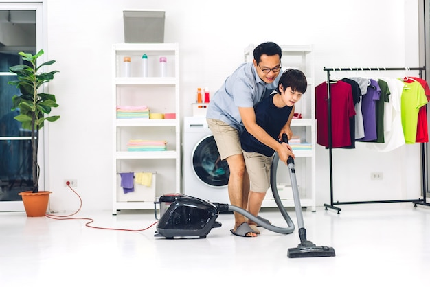 家事を楽しんでいるアジアの子供小さな男の子の息子を教えている父は、家で一緒に家を掃除しながら、掃除機で床を掃除してほこりを拭きます。家事の概念