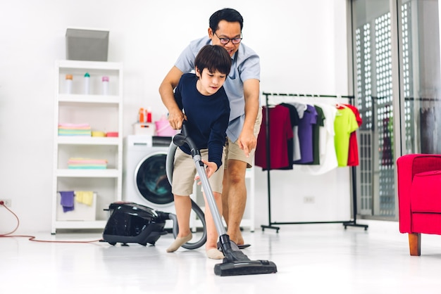 Father teaching asian kid little boy son having fun doing household chores cleaning and washing floor wiping dust with vacuum cleaner while cleaning house together at home.housework concept