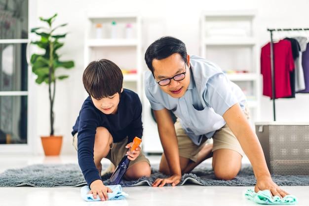 アジアの子供を教えている父は、家で一緒に家を掃除している間、消毒スプレーボトルの掃除と床拭きのほこりを雑巾で洗うことを使用しています