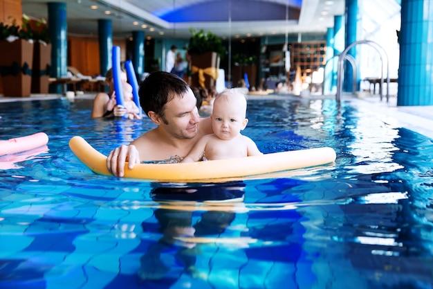 Отец учит ребенка плавать 11 месяцев ребенок в классе в бассейне здоровая семейная жизнь