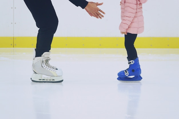 Father teaching daughter to skate at ice-skating rink
