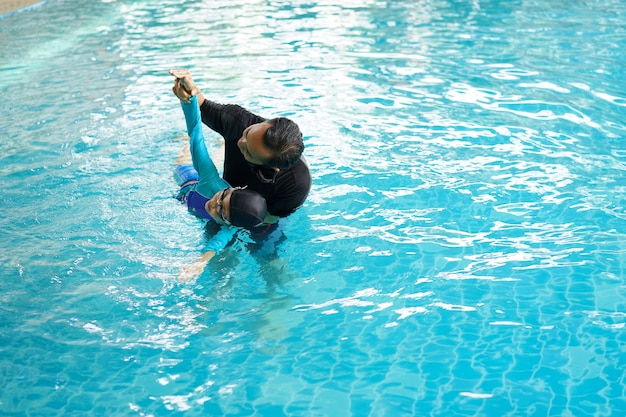 Father teaching daughter to swim in a swimming pool