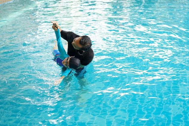 Отец учит дочь плавать в бассейне