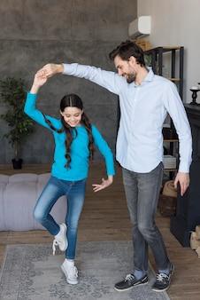 Father teaching girl to dance