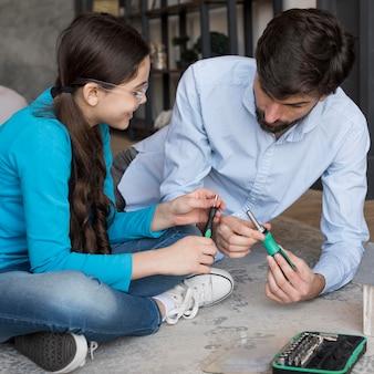 Отец учит девочку строить птичий дом