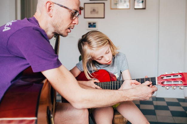 Father teaching to his daughter how to play guitar