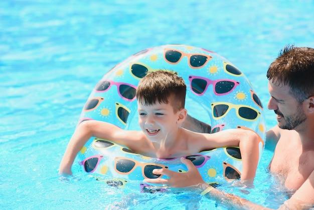 Отец учит маленького сына плавать в бассейне. концепция отпуска.