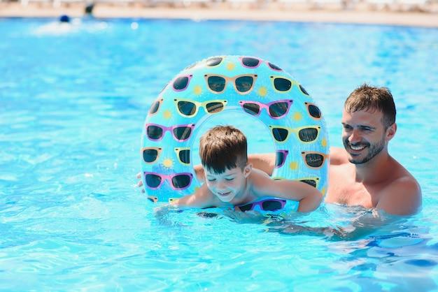Отец учит маленького сына плавать в бассейне с надувным кольцом