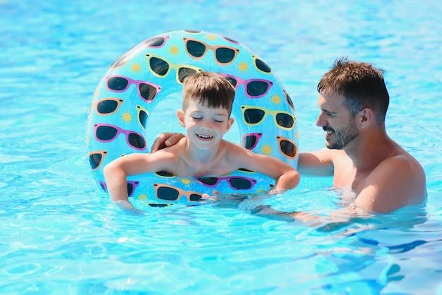 Отец учит маленького сына плавать в бассейне.