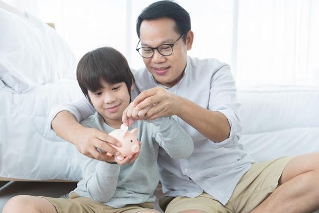 父は息子にお金の節約について教えています。自宅でピンクの節約豚瓶を持つ子供。スタジオ撮影をセットアップします。