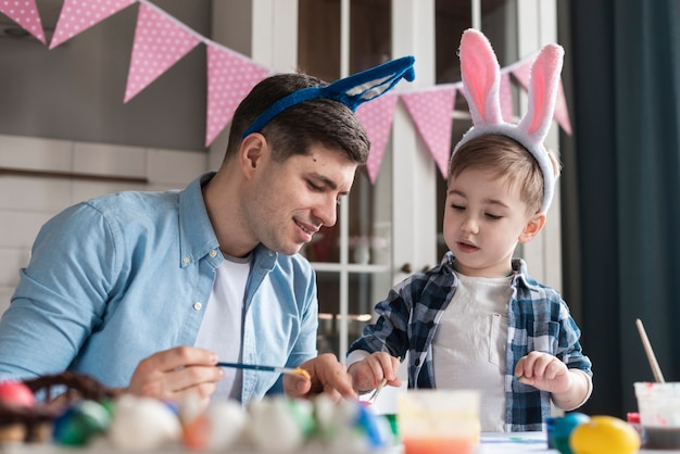 Father teaching his son how to paint eggs for easter
