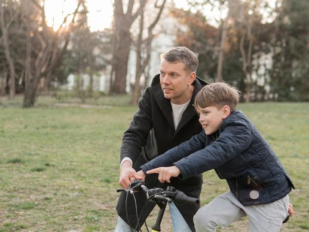 공원에서 자전거를 타는 방법을 아들에게 가르치는 아버지