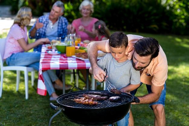 家族とバーベキューで料理の息子を教える父