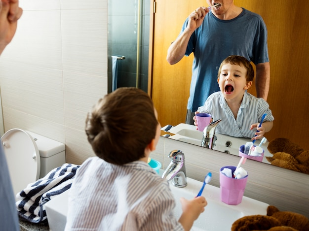 Father teaching the son how to brush his teeth