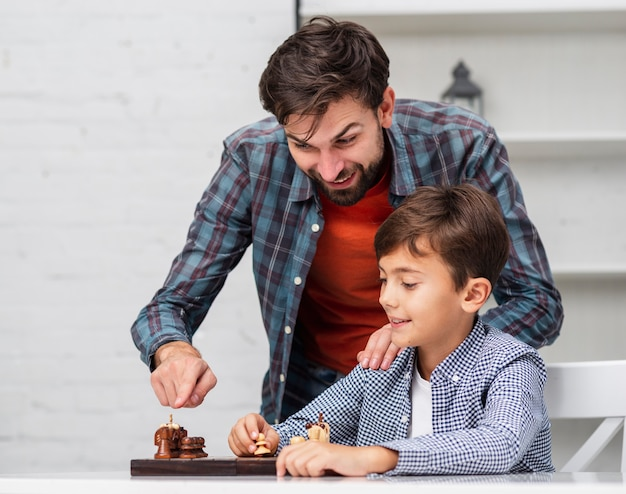 Father teaching son to play chess
